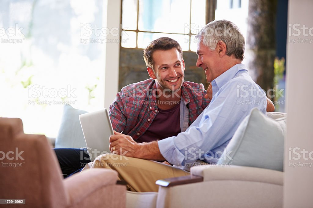 Adult Son Helping Senior Father With Computer At Home stock photo