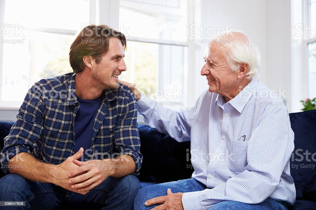 Adult Son Sitting On Sofa And Talking To Father At stock photo