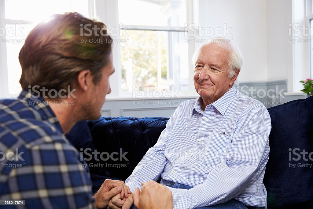 Adult Son Talking To Depressed Father At Home stock photo