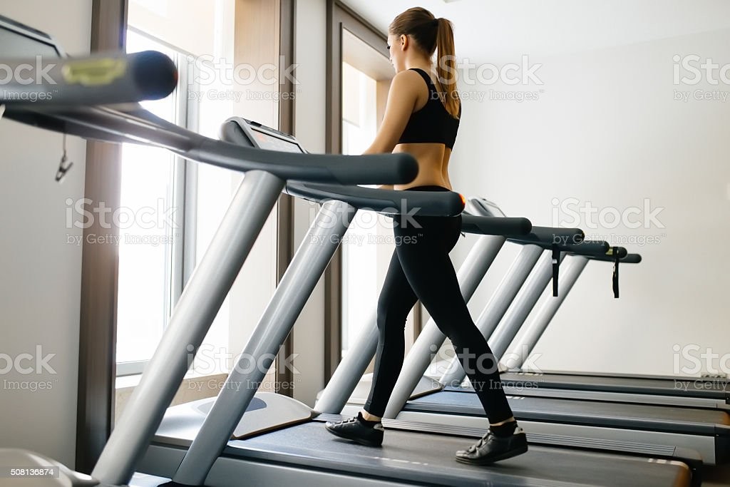 Adult sport woman walking on treadmill in gym stock photo