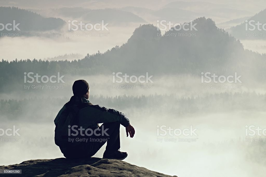 Adult sportsman on cliff above valley watch into misty landscape stock photo