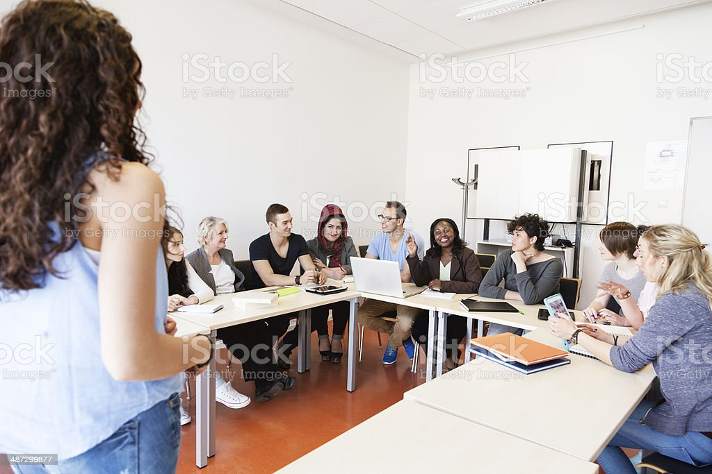 adult students and teacher in classroom discussion seminar stock photo