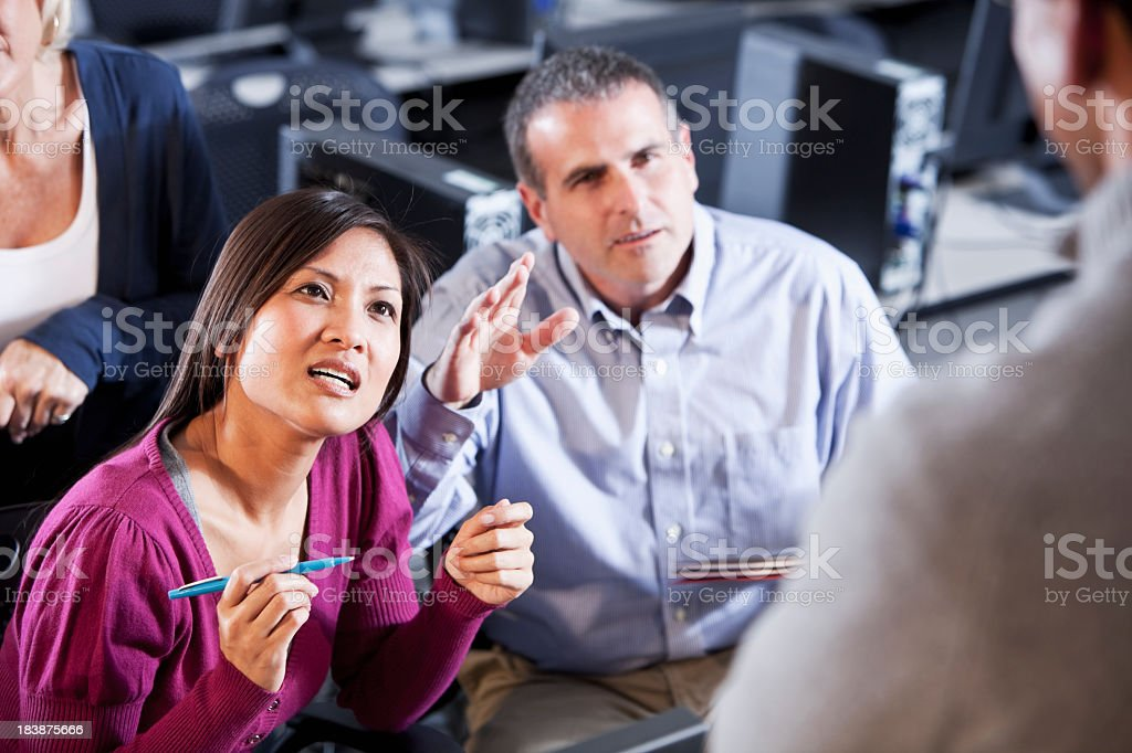 Adult students asking questions in computer lab stock photo