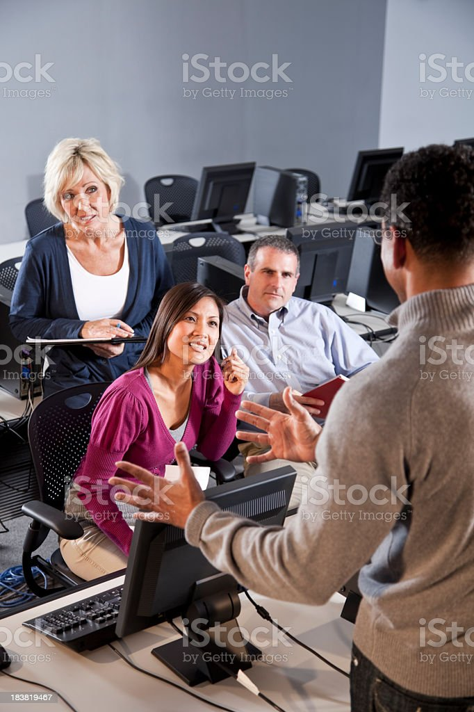 Adult students listening to instructor in computer classroom royalty-free stock photo