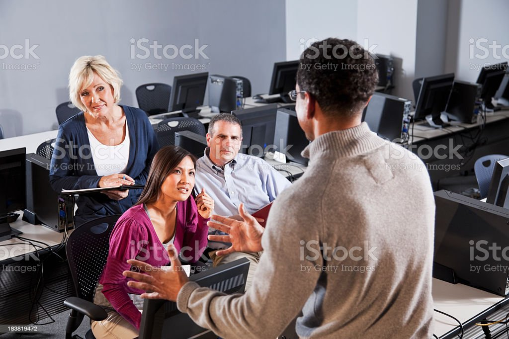 Adult students listening to instructor in computer classroom stock photo