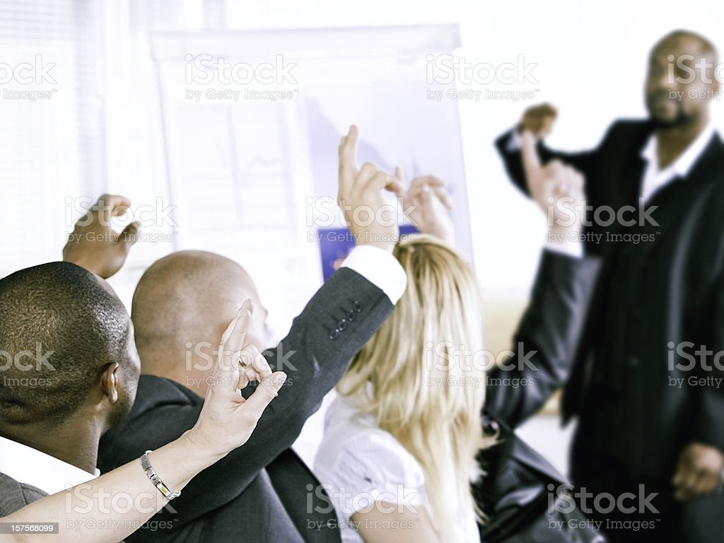 Adult students participating and raising hands at a meeting royalty-free stock photo