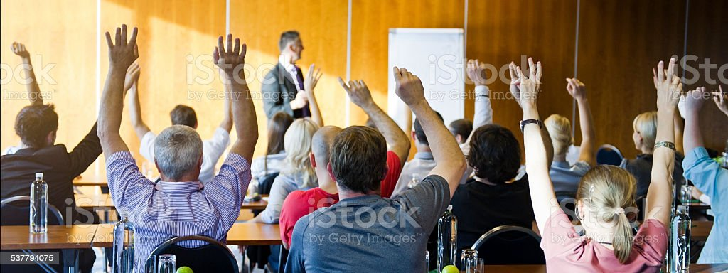 Adult students raising hands on seminar stock photo