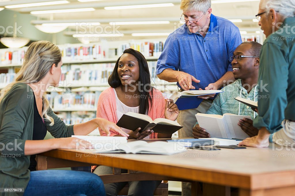 Adult students studying  together in library stock photo
