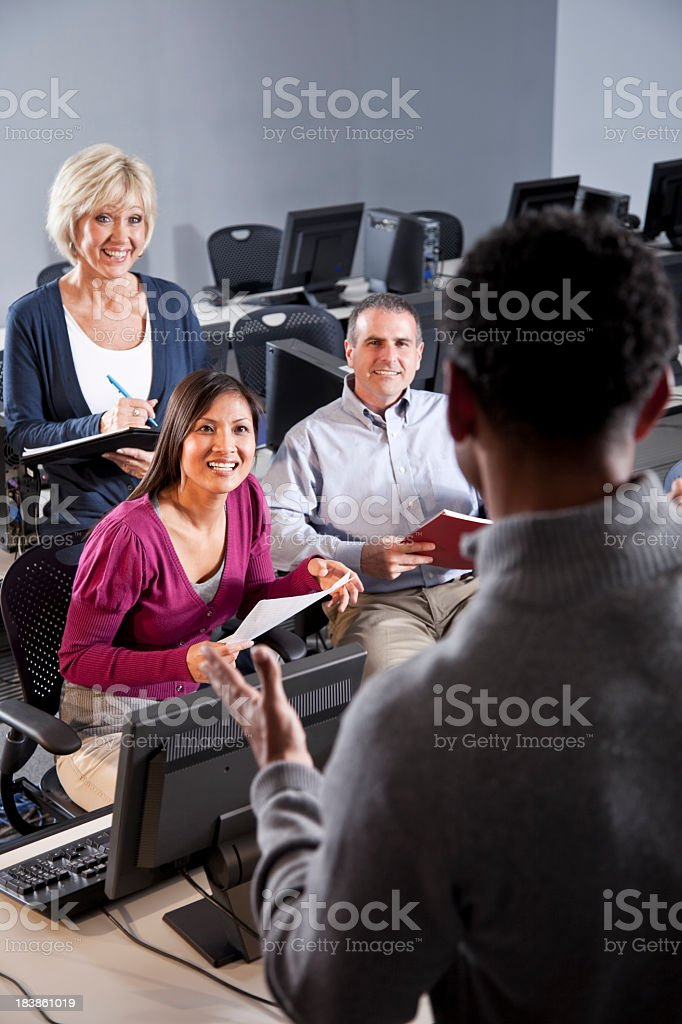 Adult students taking notes in computer classroom stock photo