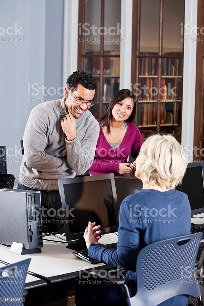 Adult students talking in computer lab stock photo