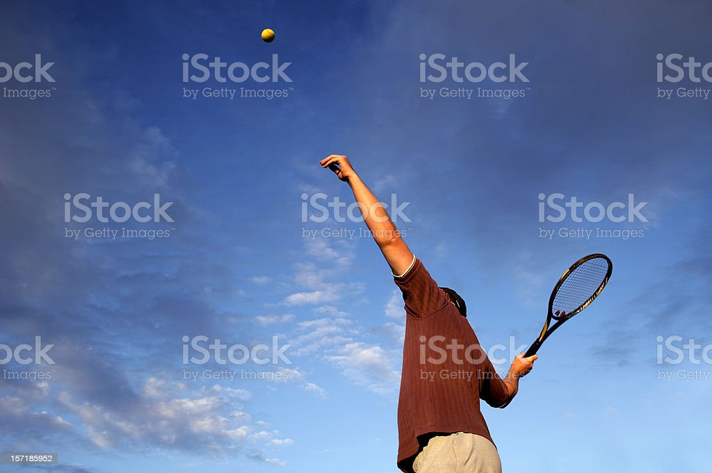 Adult tennis player serving royalty-free stock photo