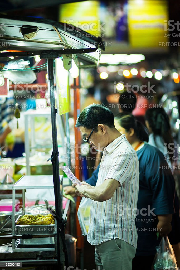 Adult thai man with glasses buying dinner stock photo