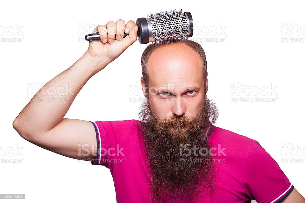Adult unhappy man hand holding comb on bald head stock photo