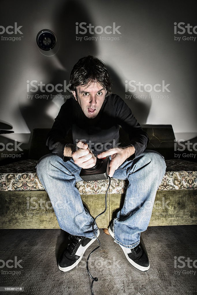Adult videogamer playing at night stock photo