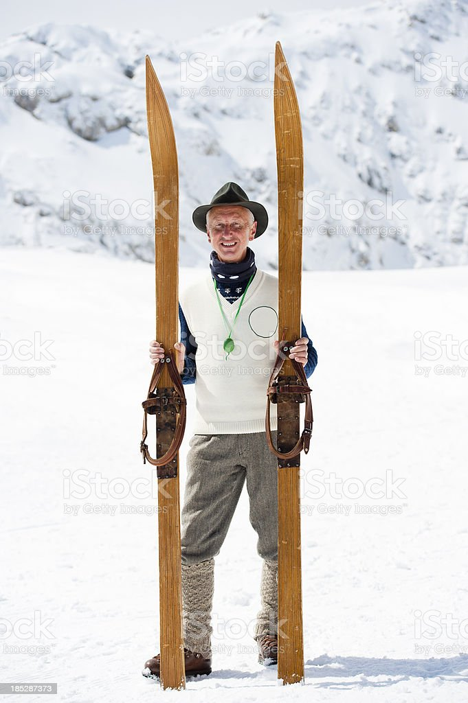 Adult vintage skier posing in the mountains royalty-free stock photo