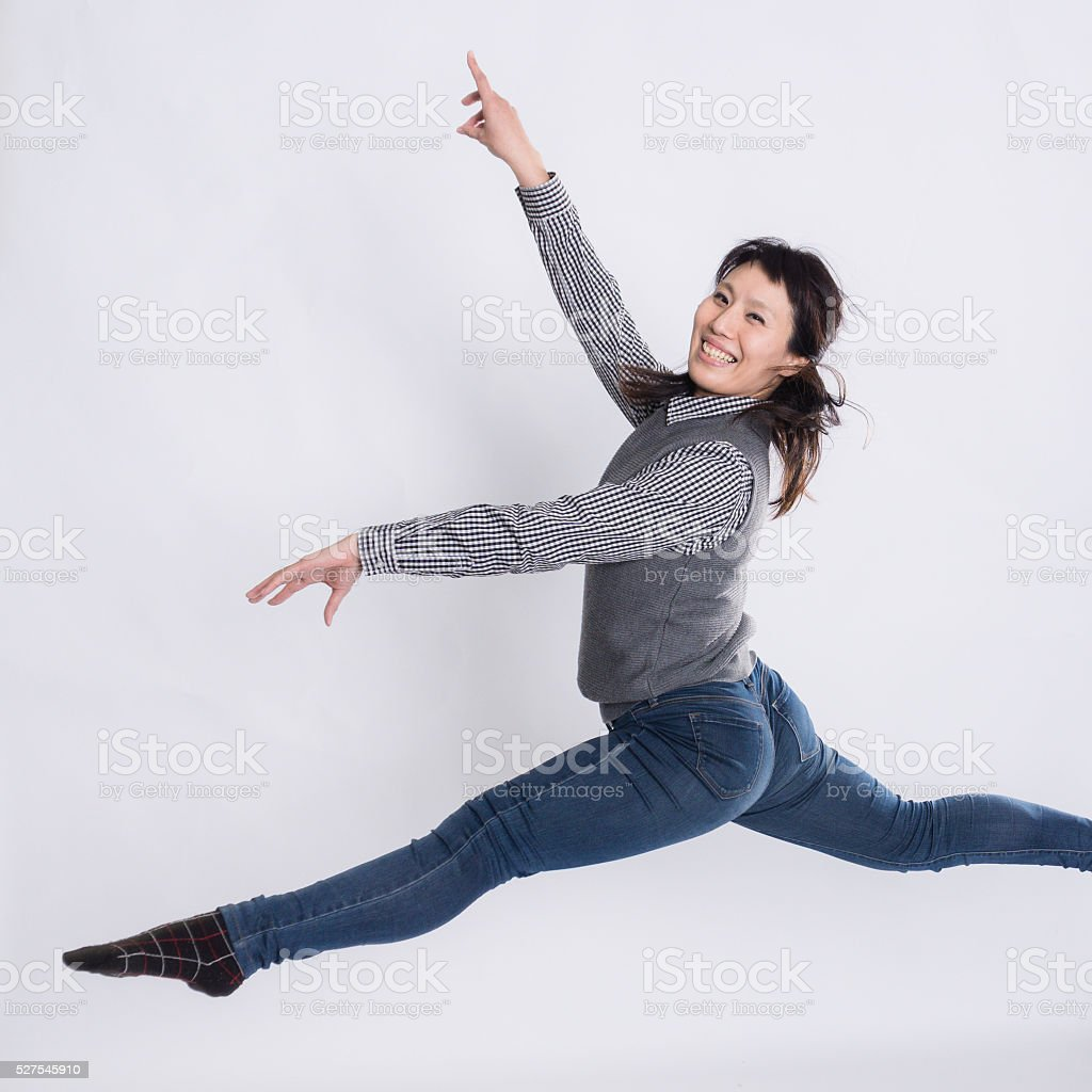 Adult woman doing jumping splits on a white background stock photo
