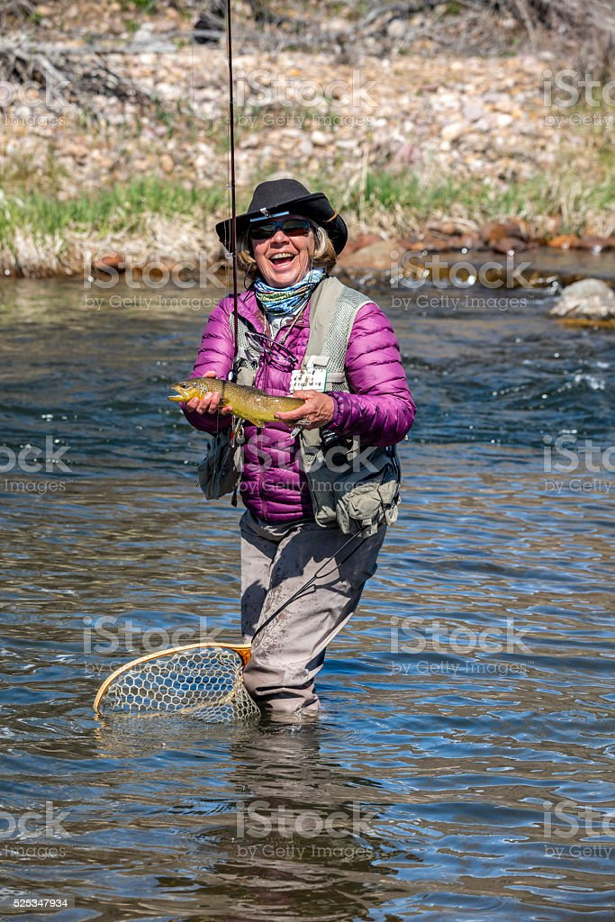 Adult Woman Fly-Fisher Holding a Brown Trout stock photo