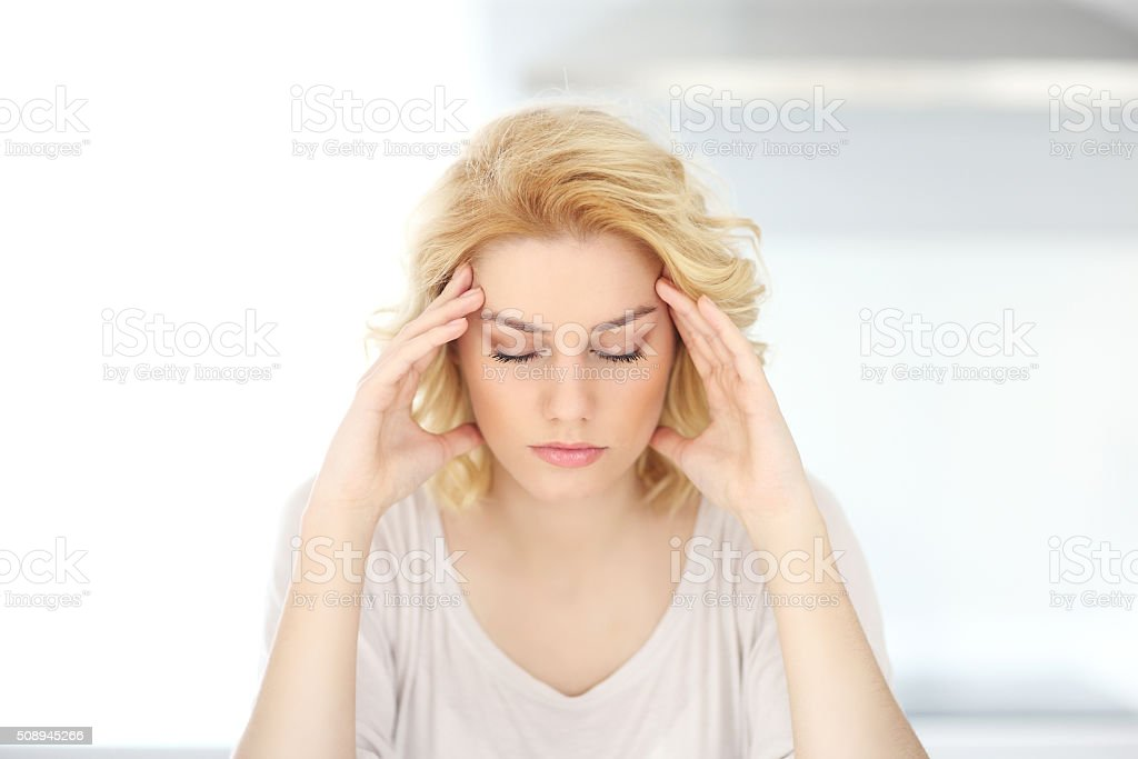 Adult woman having headache at home stock photo