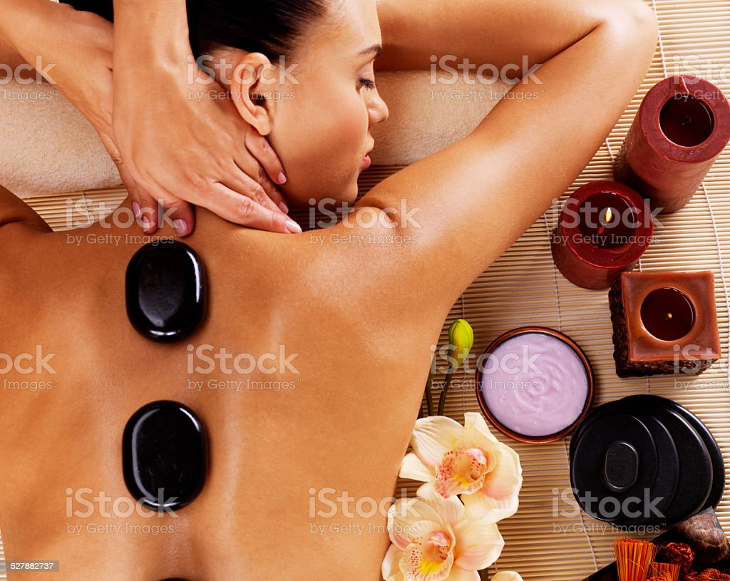 Adult woman having hot stone massage in spa salon stock photo