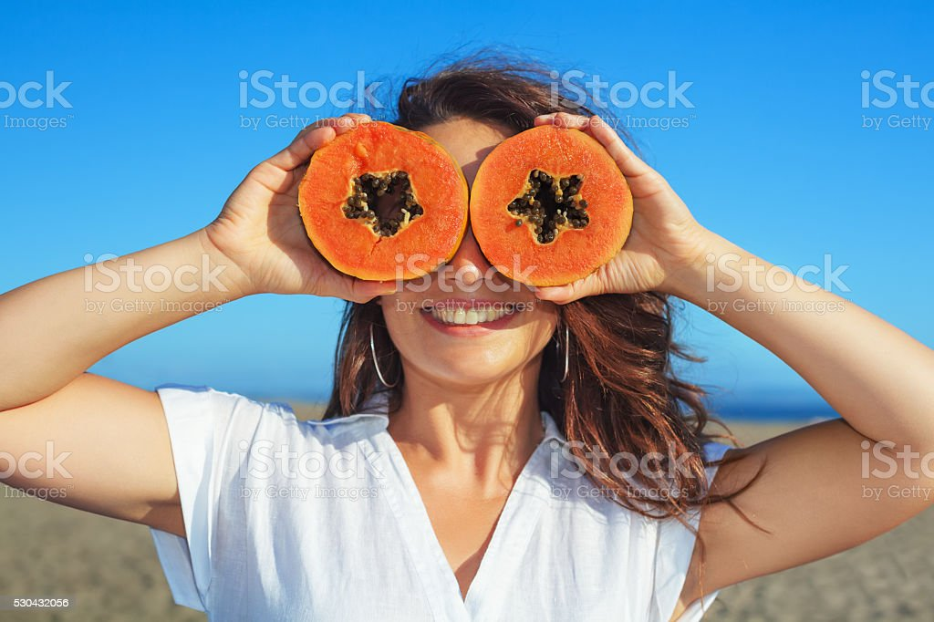 Adult woman hold in hands ripe fruit - orange papaya stock photo