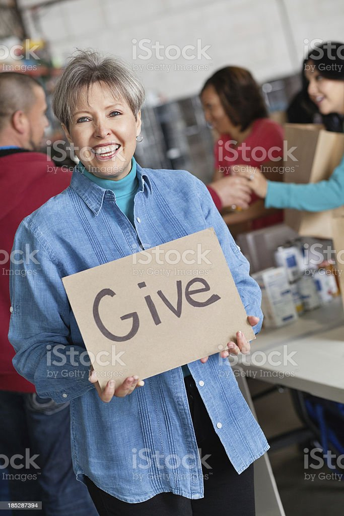 Adult woman holding Give sign at food donation center royalty-free stock photo