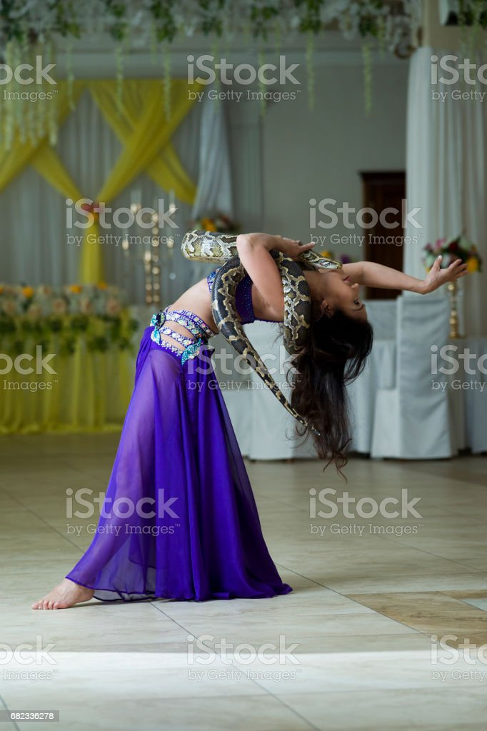 Adult woman in stage costume performs with big snake