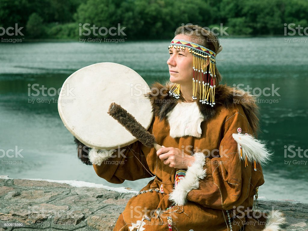 Adult woman in traditional Koryak dress holding a tambourine stock photo