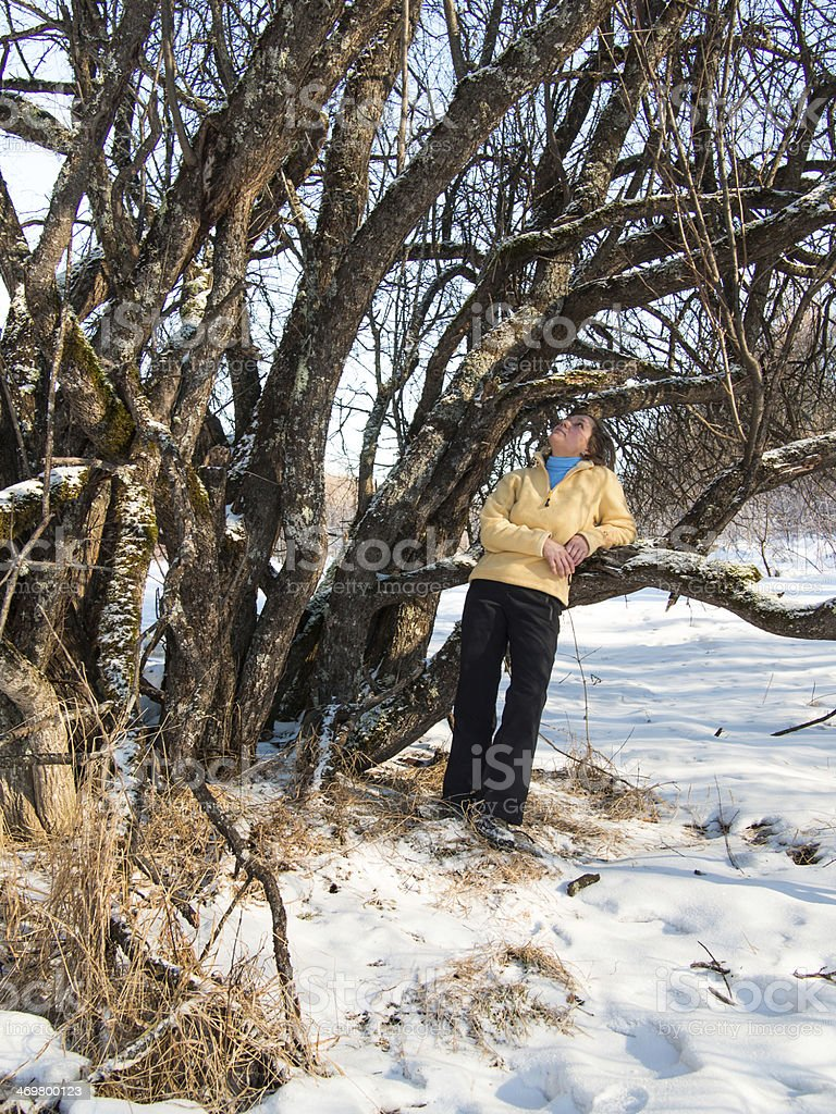 Adult woman leaned against on a tree stock photo