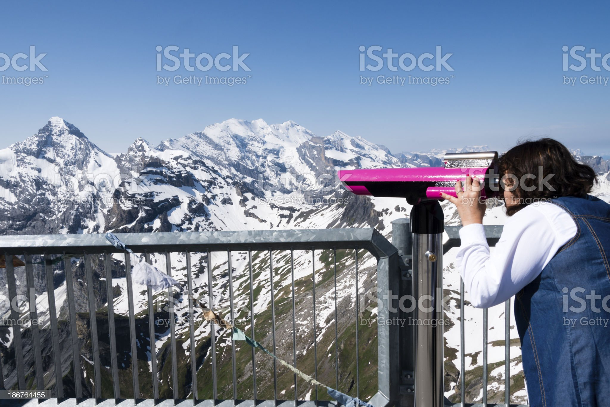 Adult woman looking through large binoculars observing snow cove royalty-free stock photo