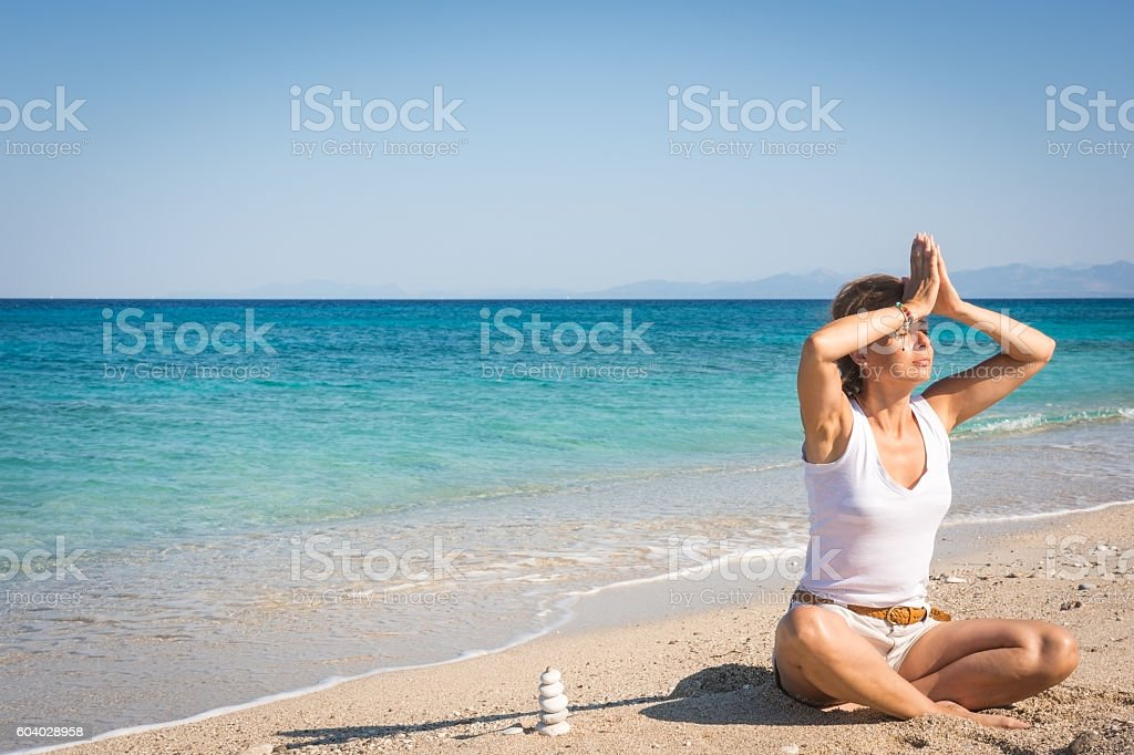 Adult woman meditating on the beach in peace, morning stock photo