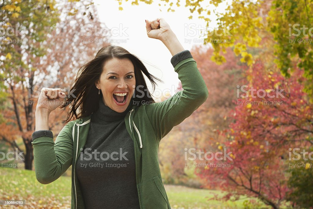 Adult woman outdoors with fists in the air stock photo