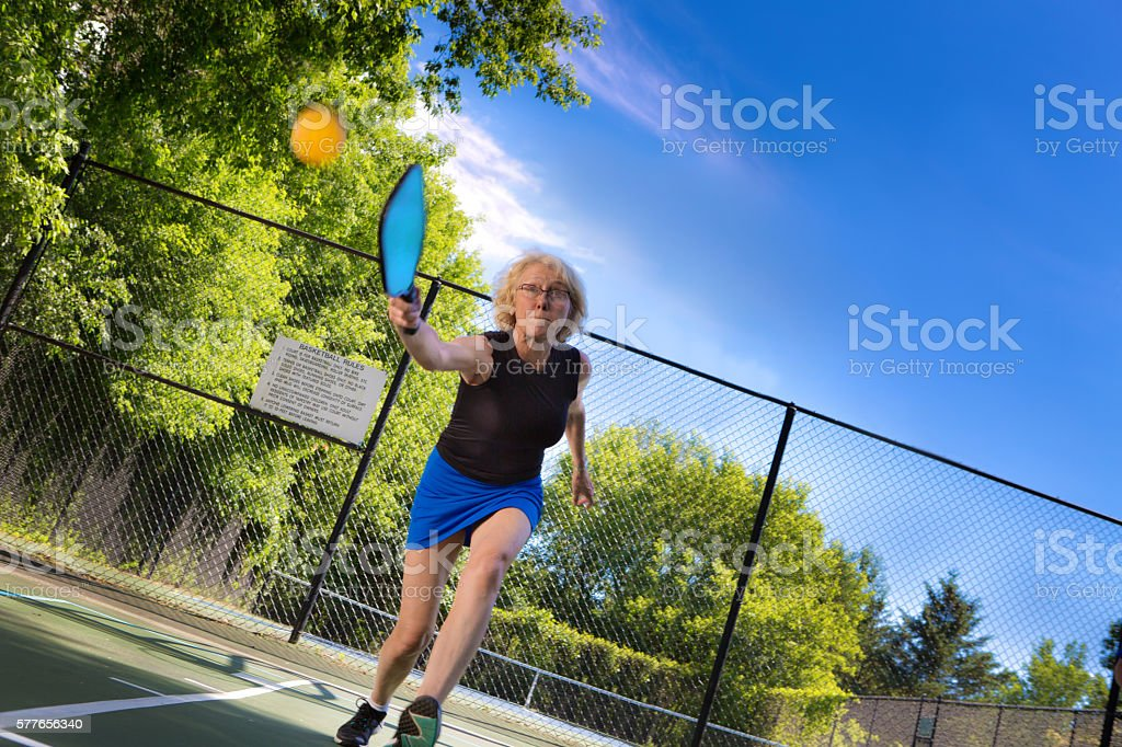 Adult Woman Pickleball Player Playing Pickleball in Court stock photo