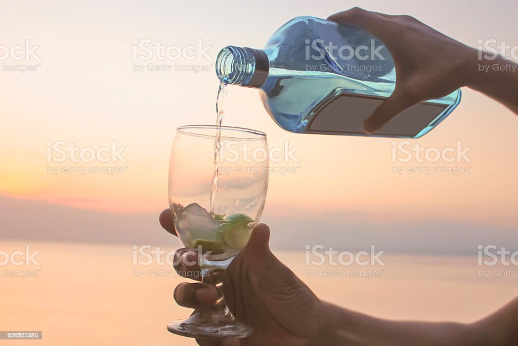 Adult woman pouring gin from the bottle stock photo