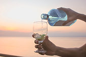 adult woman pouring gin with sunset backgrounds