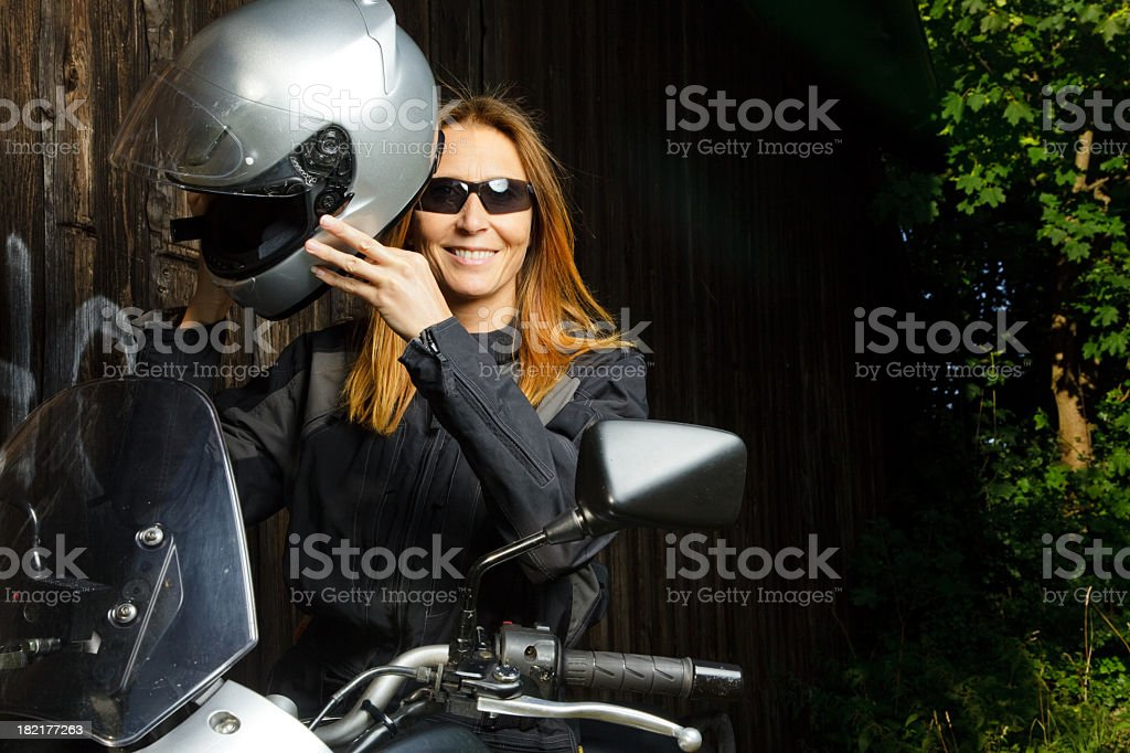 adult woman putting on her helmet royalty-free stock photo