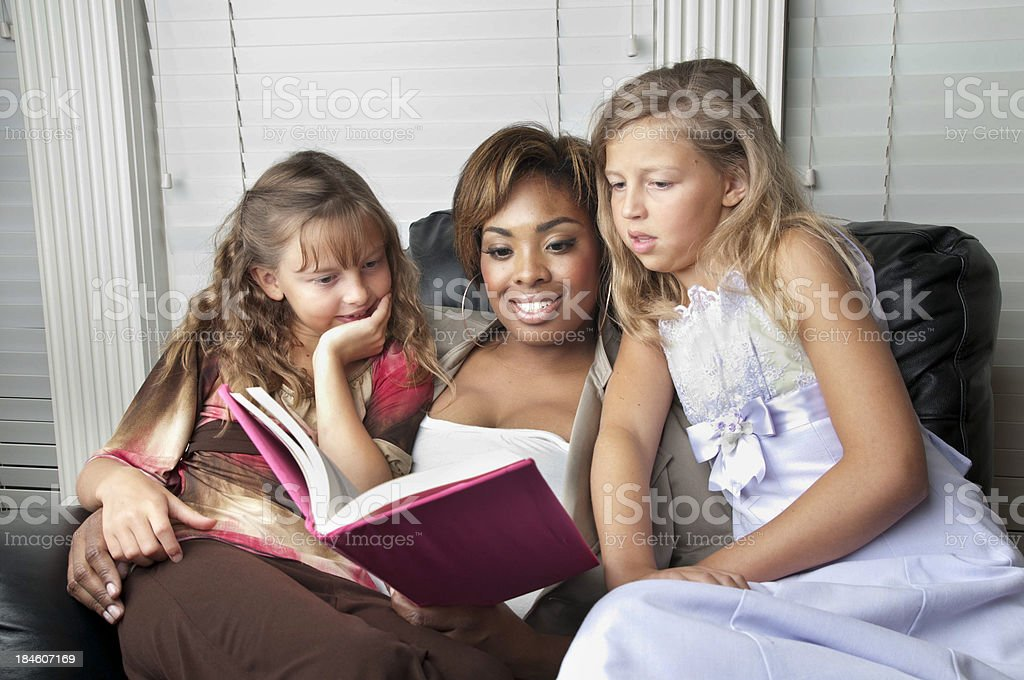 Adult Woman Reads to Young Girls Sitting in her Lap stock photo