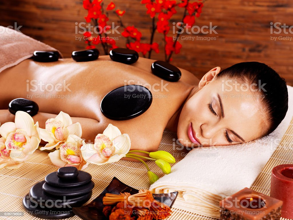 Adult woman relaxing in spa salon with hot stones on stock photo