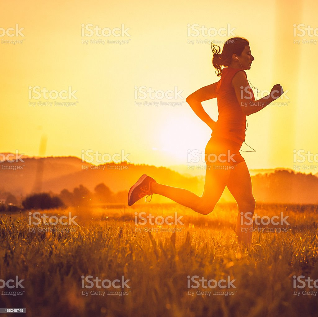Adult woman running outdoors stock photo