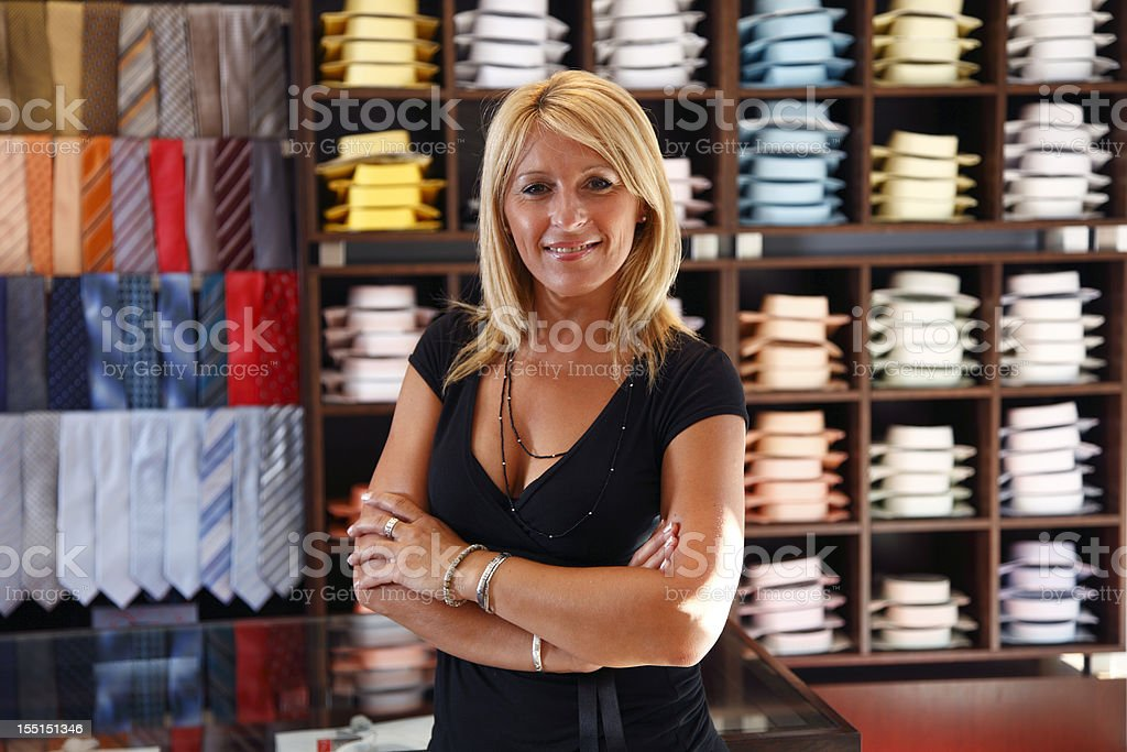 Adult woman - sales clerk in shirts store royalty-free stock photo
