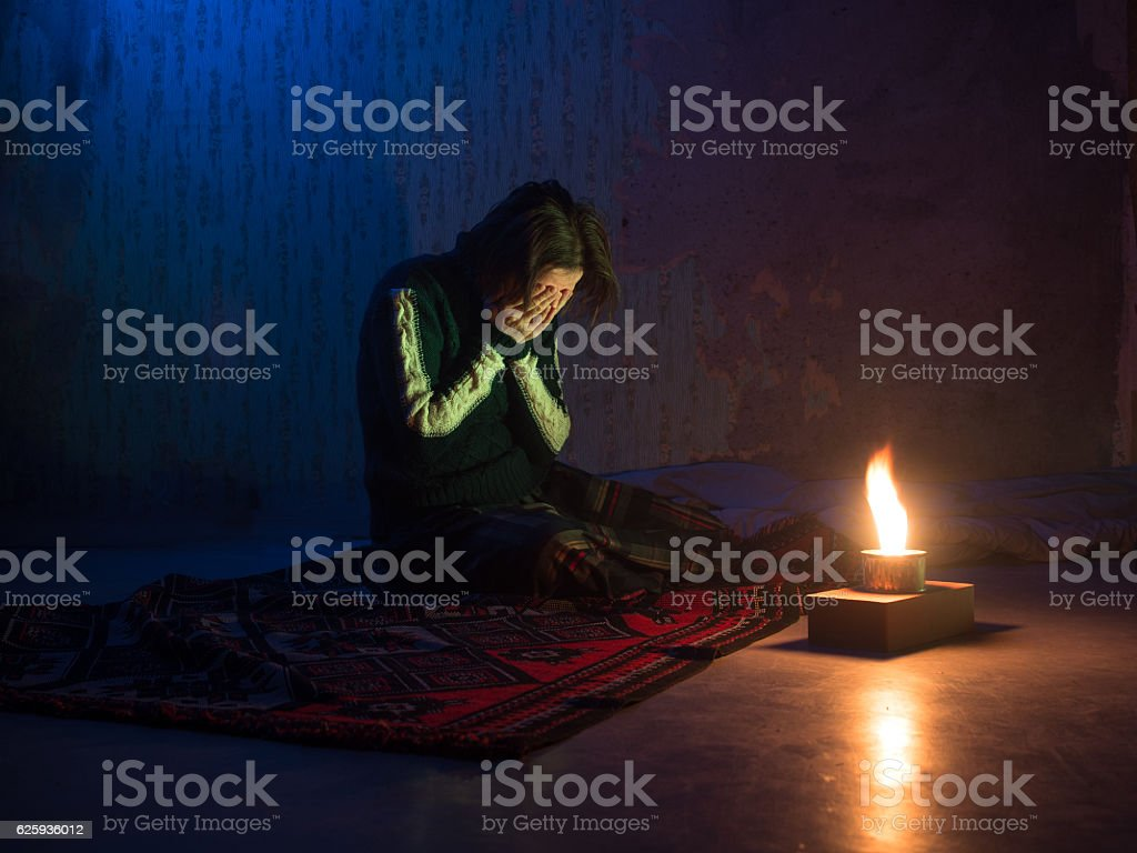 Adult woman sitting on floor and crying  and burning candle stock photo