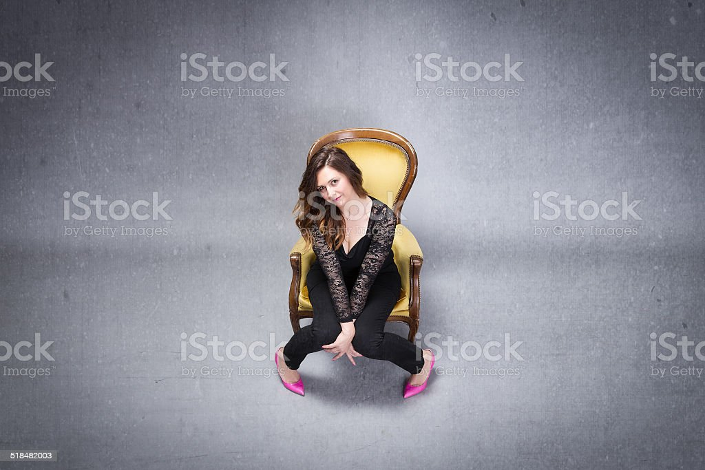 adult woman sitting on yellow sofa stock photo