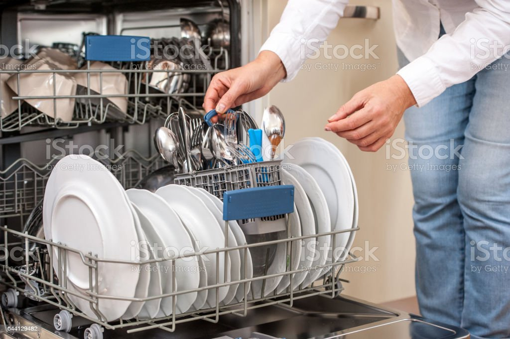 Adult Woman Unloading Dishwasher In The Kitchen stock photo
