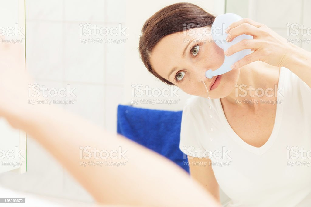 adult woman using neti pot stock photo