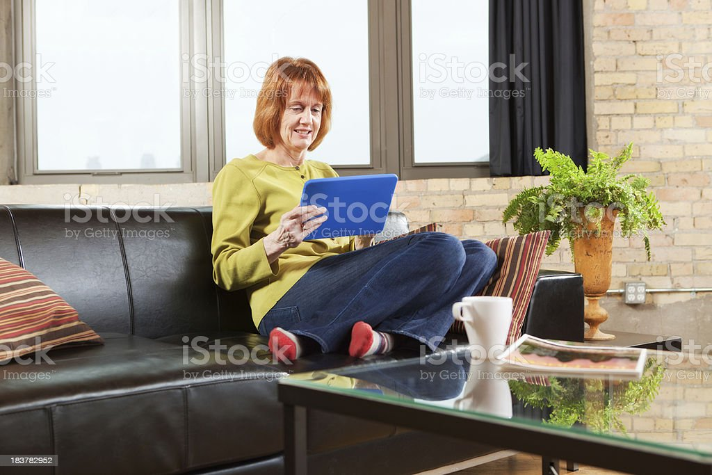 Adult Woman Using Tablet Computer in Condominium Home Hz royalty-free stock photo