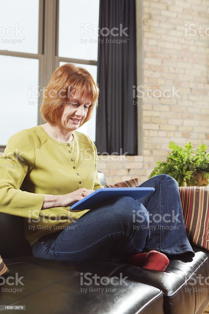 Adult Woman Using Tablet Computer in Condominium Loft Apartment Home royalty-free stock photo
