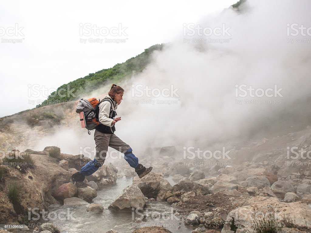 Adult woman with backpack jumping ove hot stream smoking crater stock photo