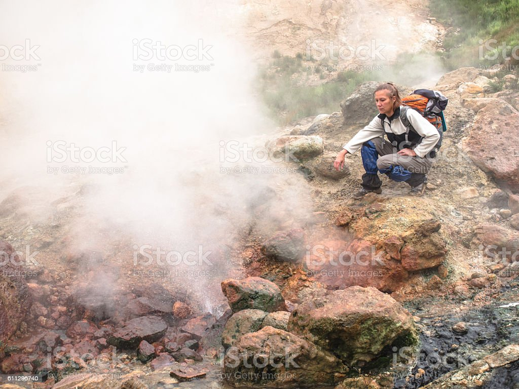 Adult woman with backpack sitting in geyser smoking crater volcano stock photo