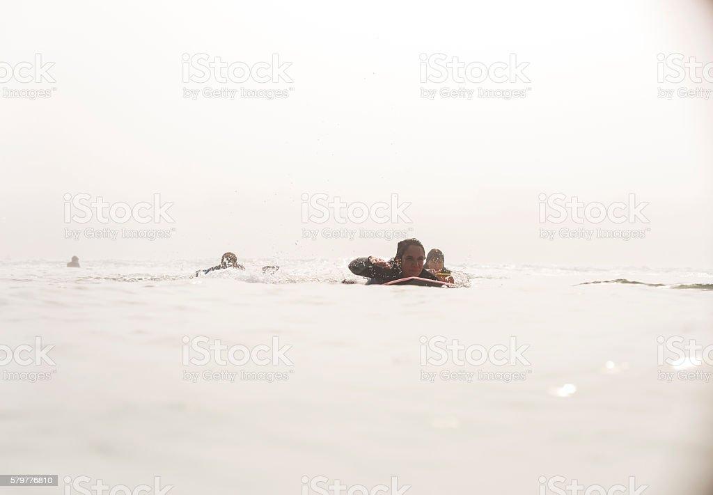 Adult Women Bodyboarding In The Ocean stock photo