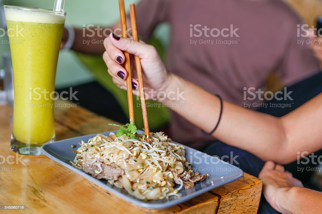 Adult women eating pad thai noodle stock photo