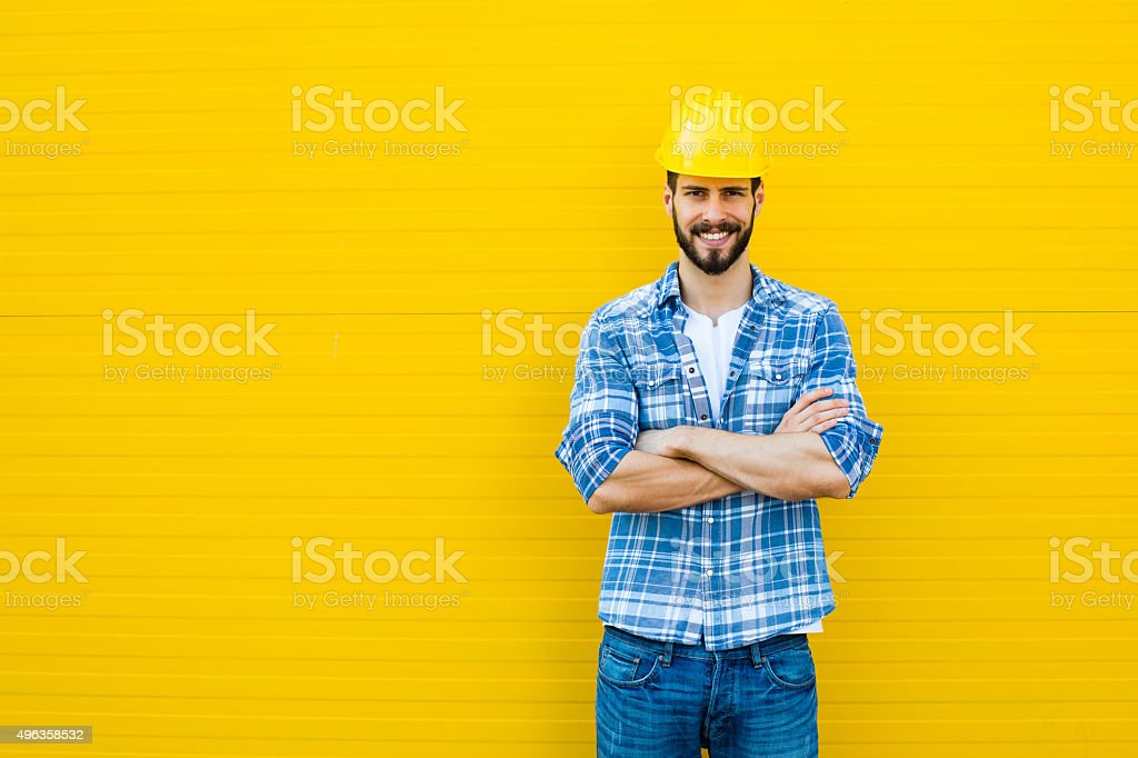 adult worker with helmet on yellow wall stock photo